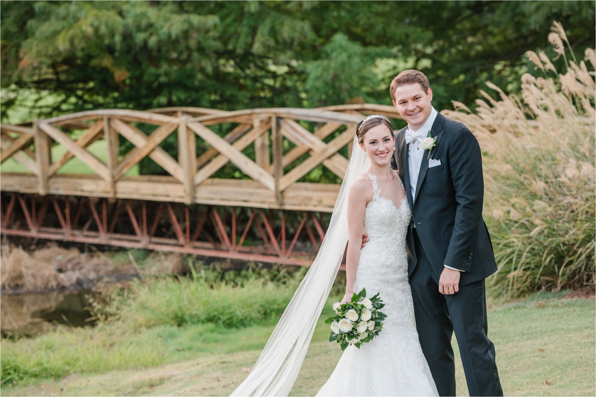 Bride and groom in front of bridge at greensboro country club