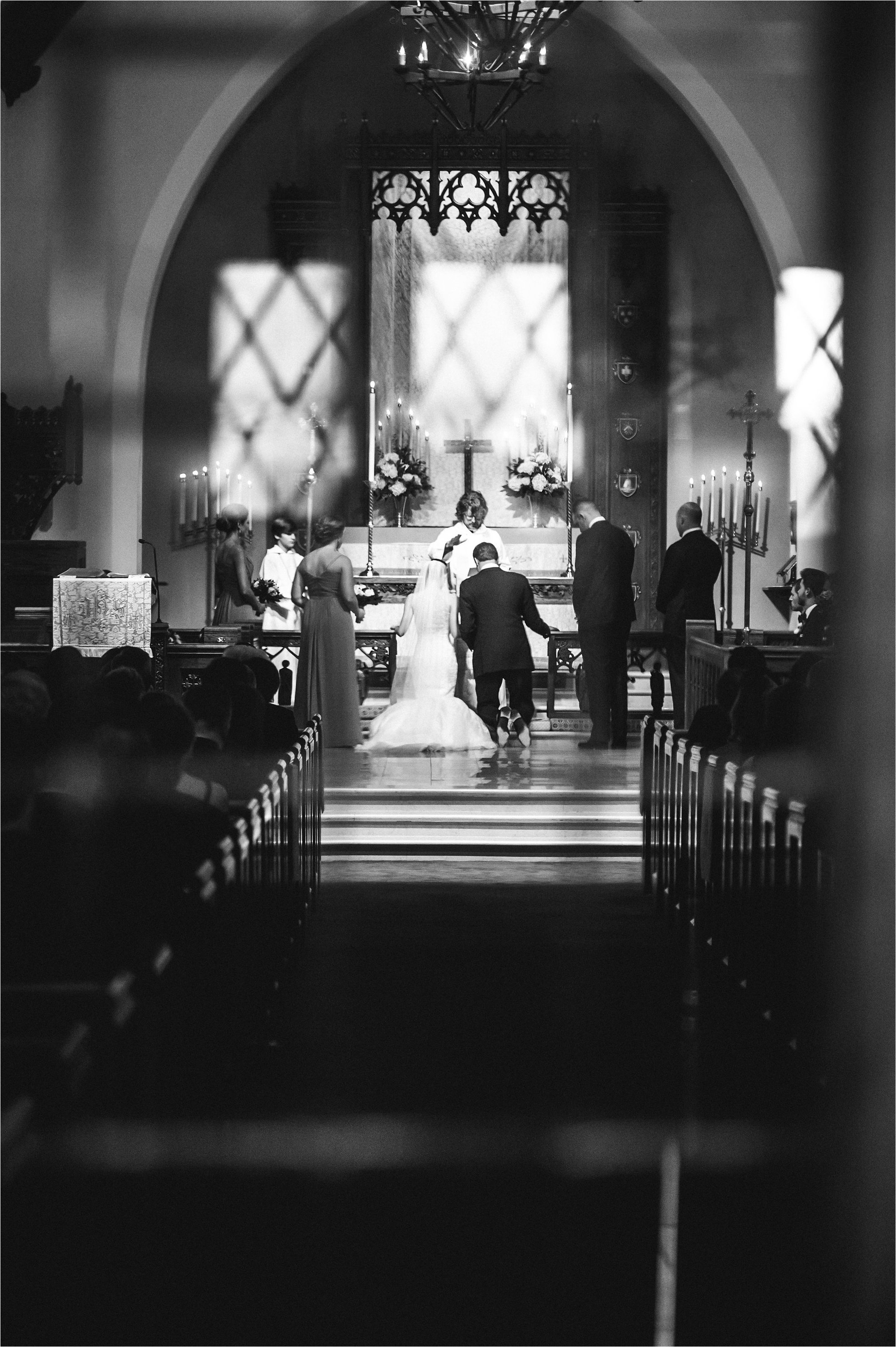 Black and white photo of bride and groom kneeling at altar