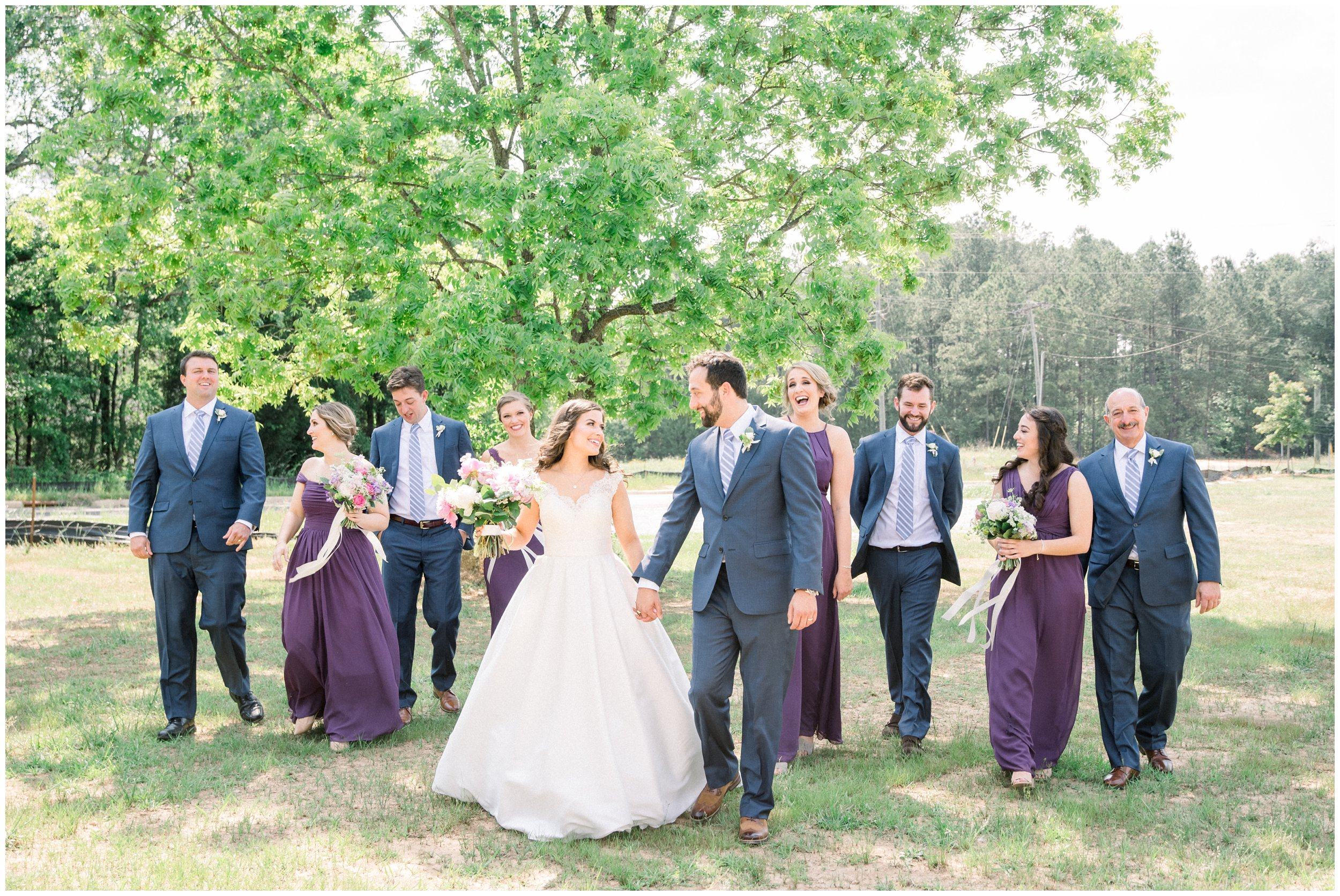 wedding party walking with newlyweds laughing