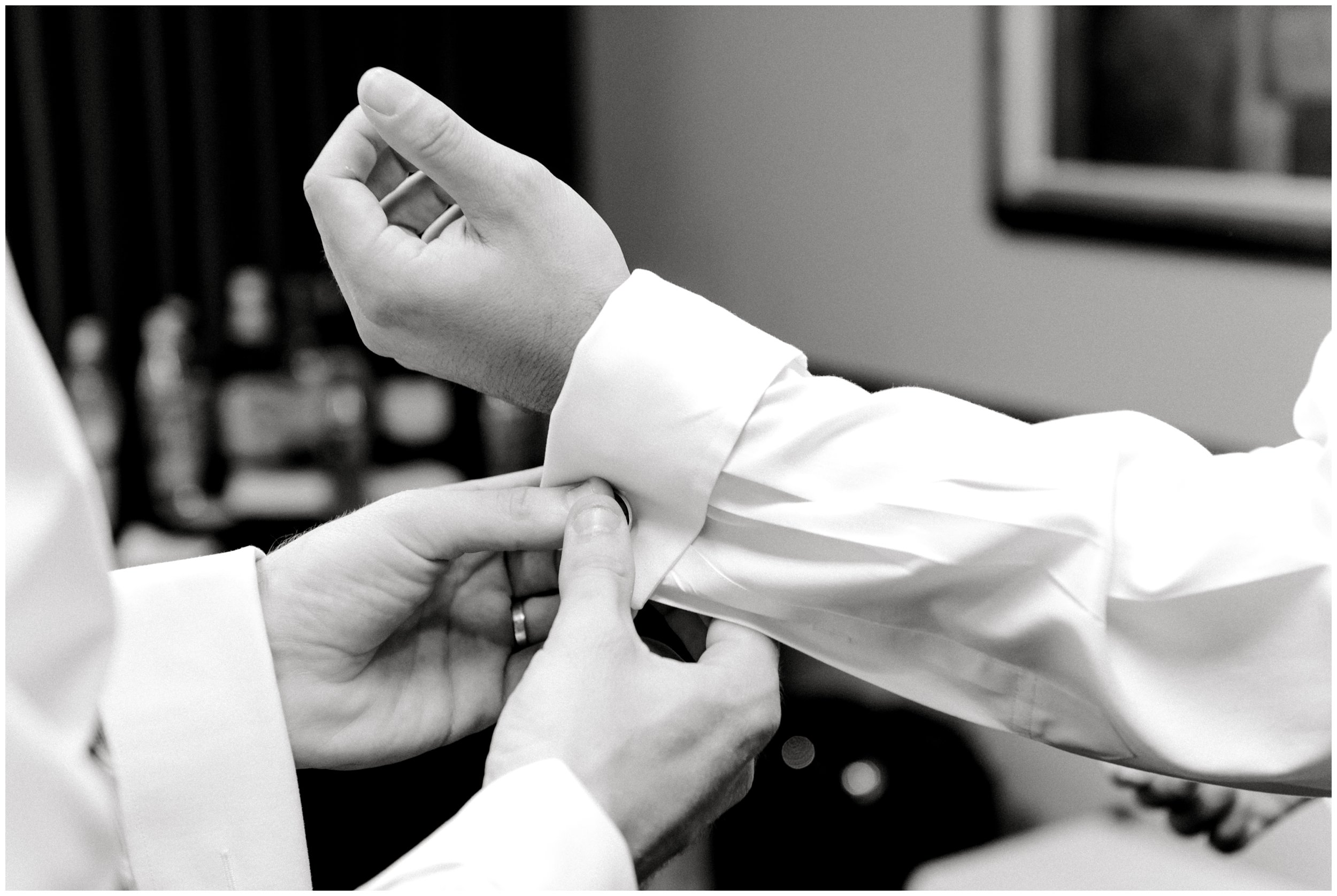 groomsman helping with groom's cufflinks