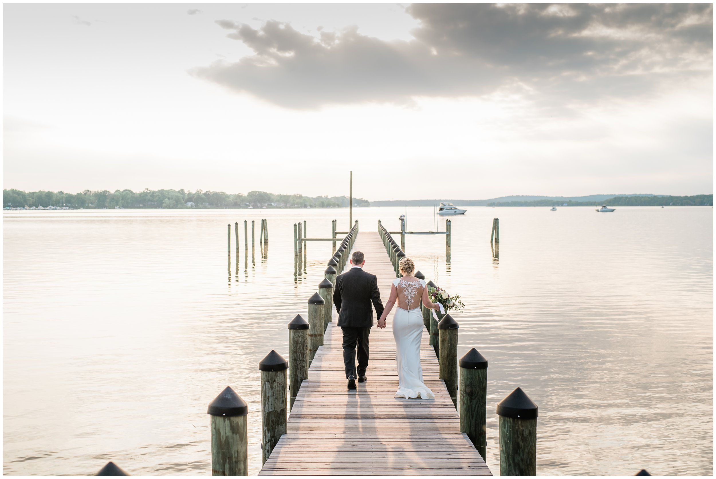 husband and wife walking on dock at sunset