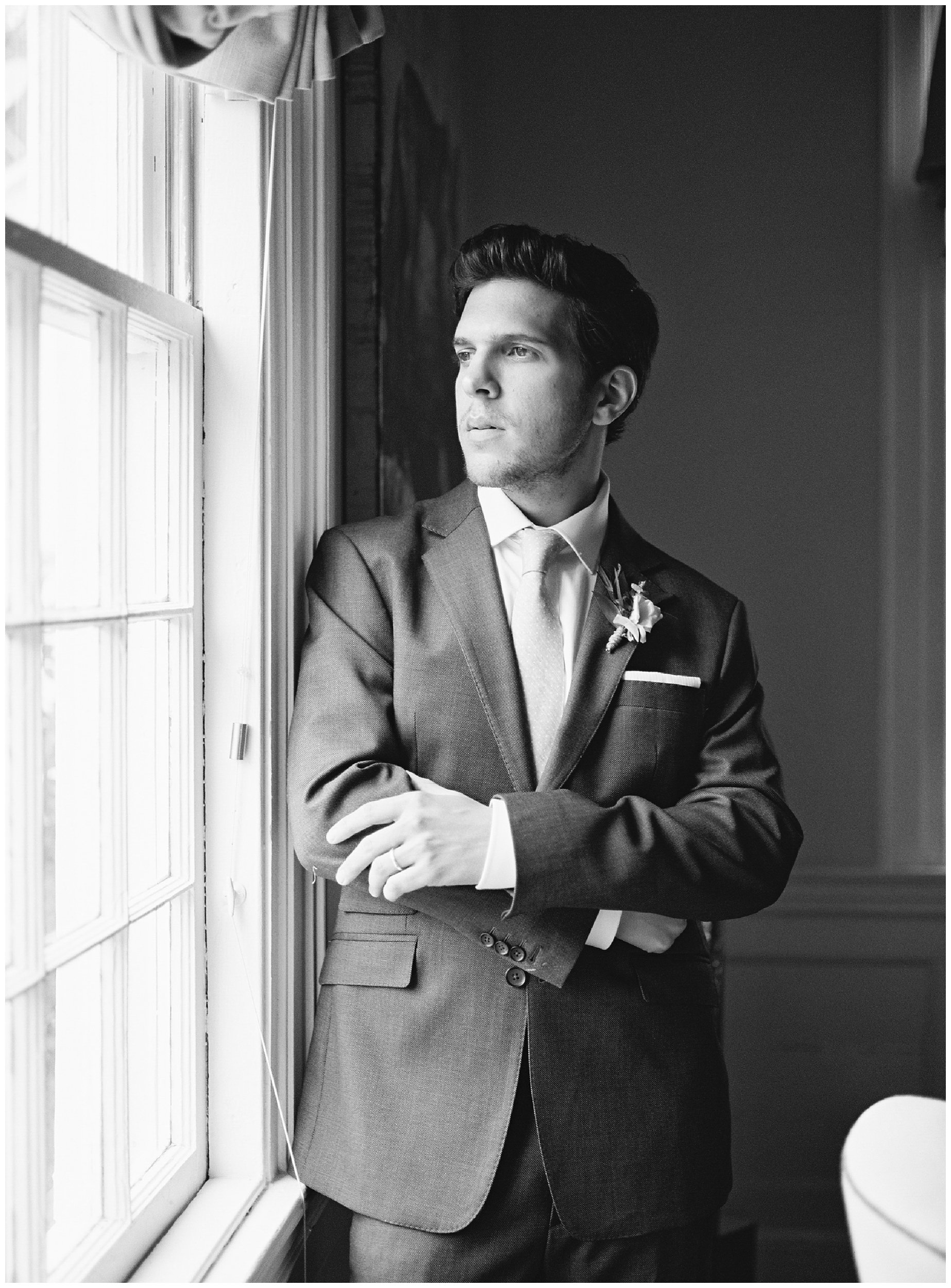 moody groom photo next to window