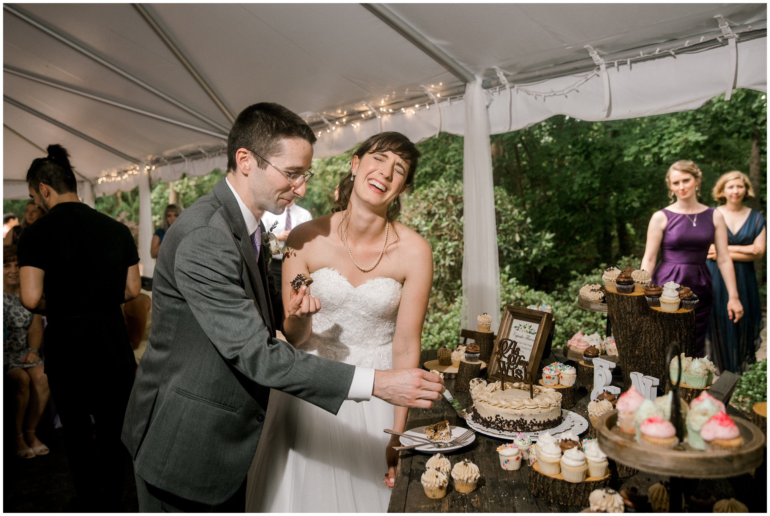 bride and groom laughing, cake cutting