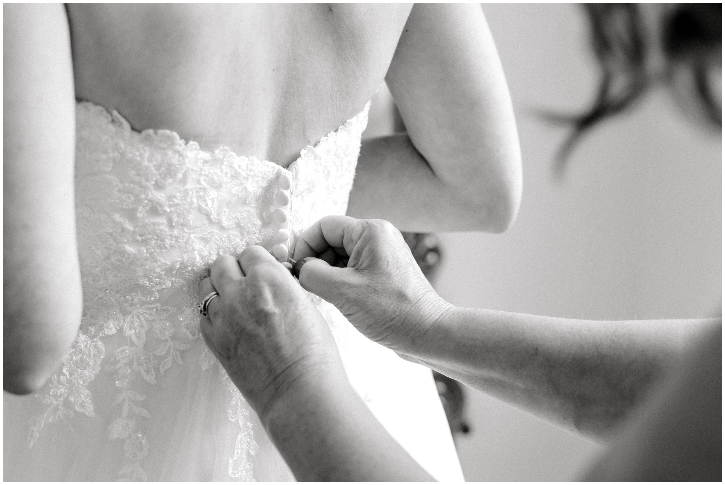 mother of the bride buttoning up wedding dress