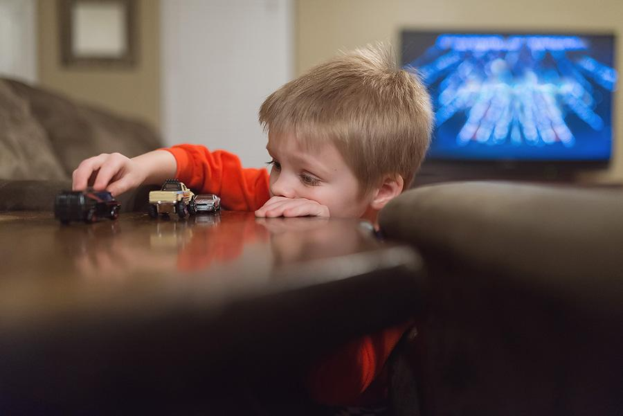 boy playing with matchbox cars