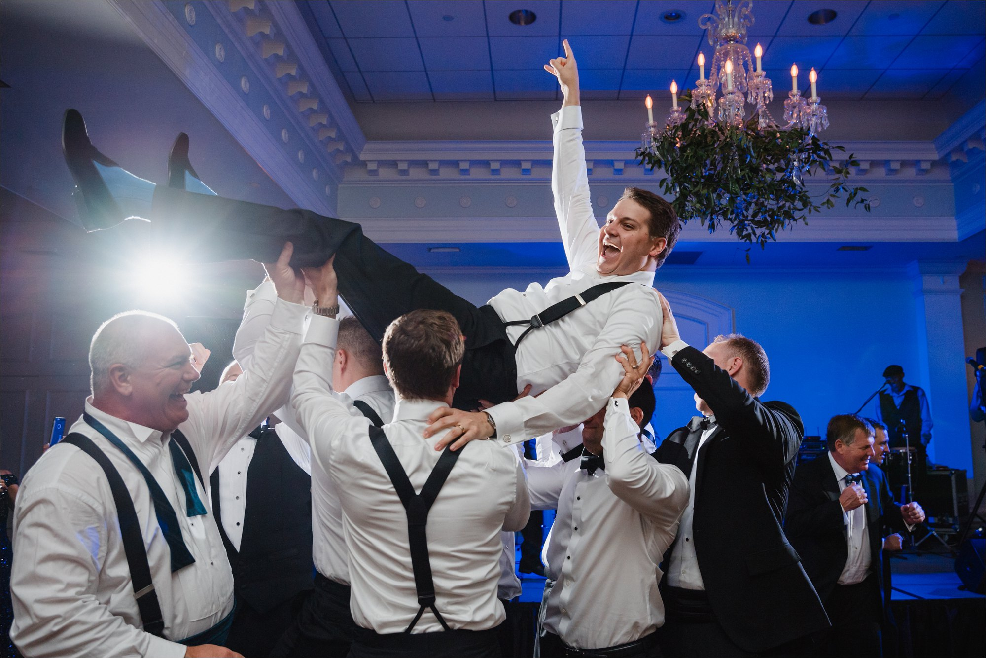 groom lifted up dancing at wedding
