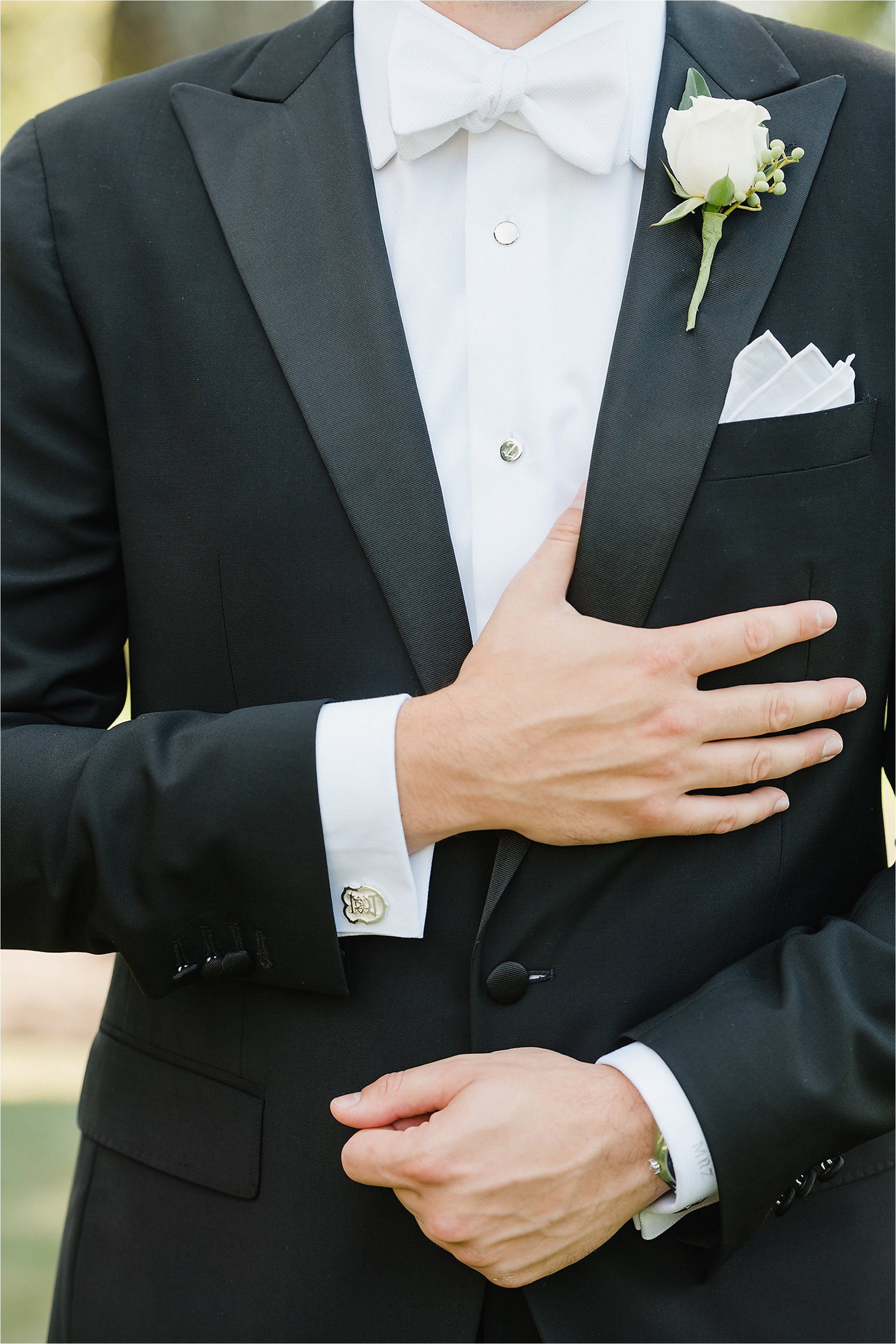 Close up of groom's black tux