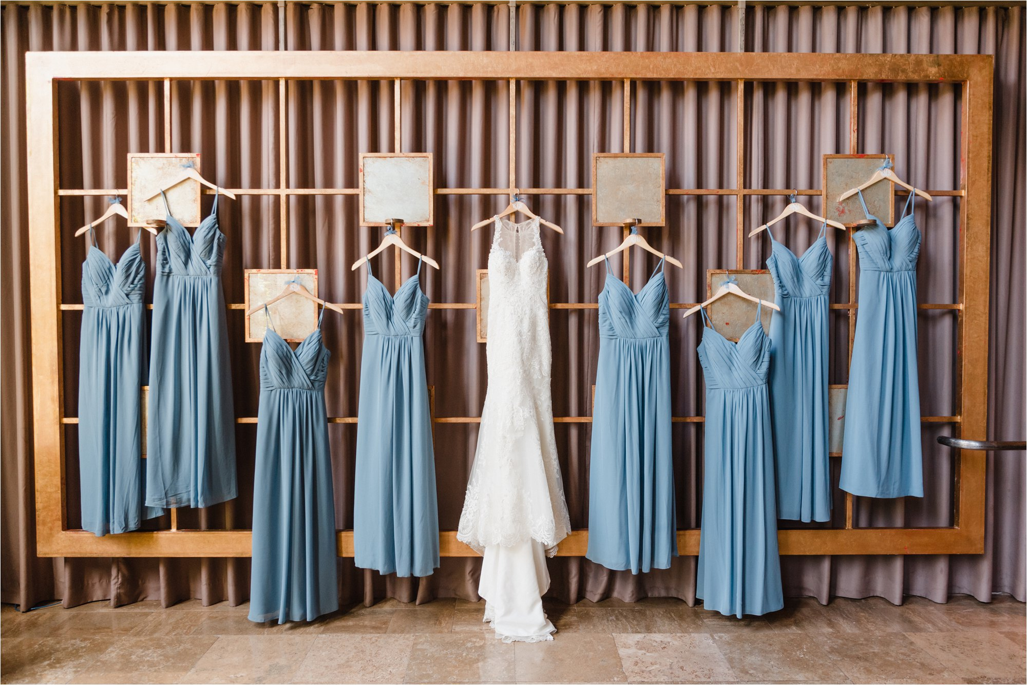 wedding dress hanging with blue bridesmaid dresses