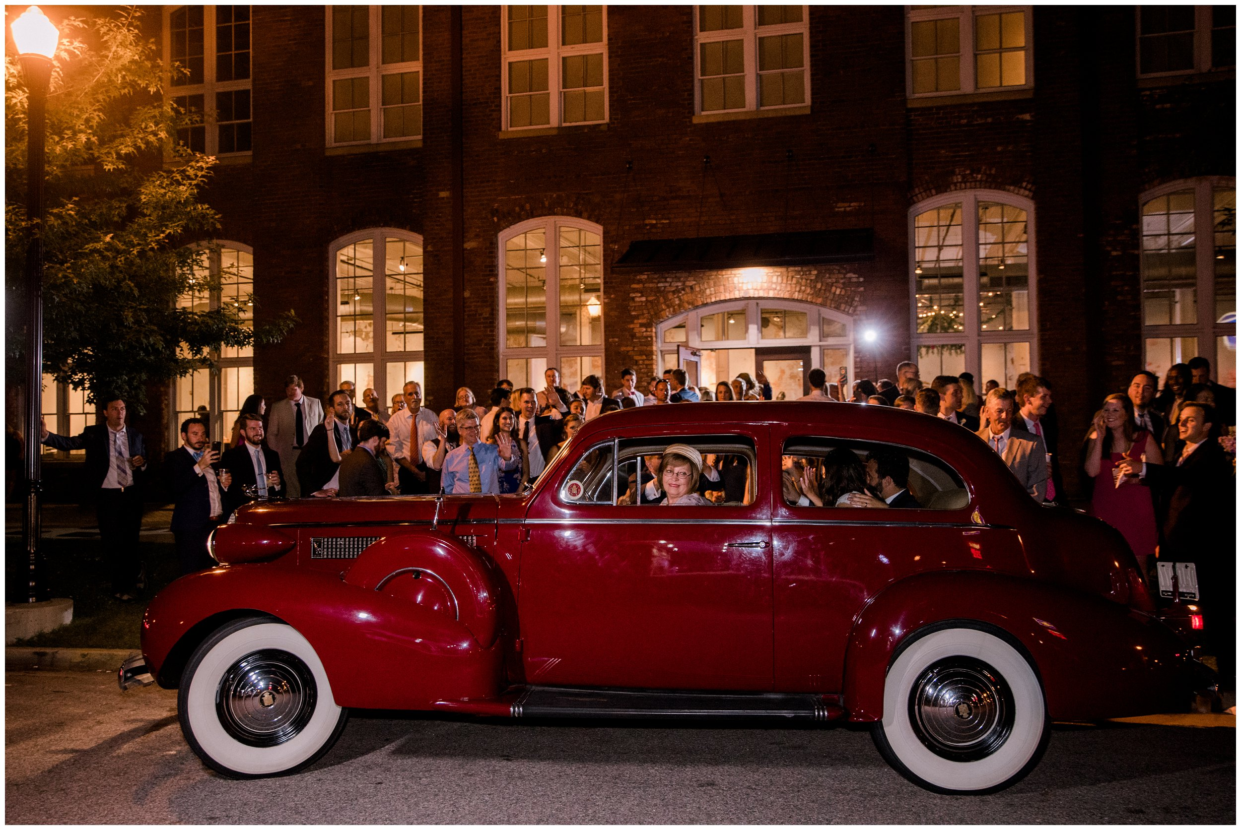 bride and groom ride away from columbia wedding venue in a vintage car