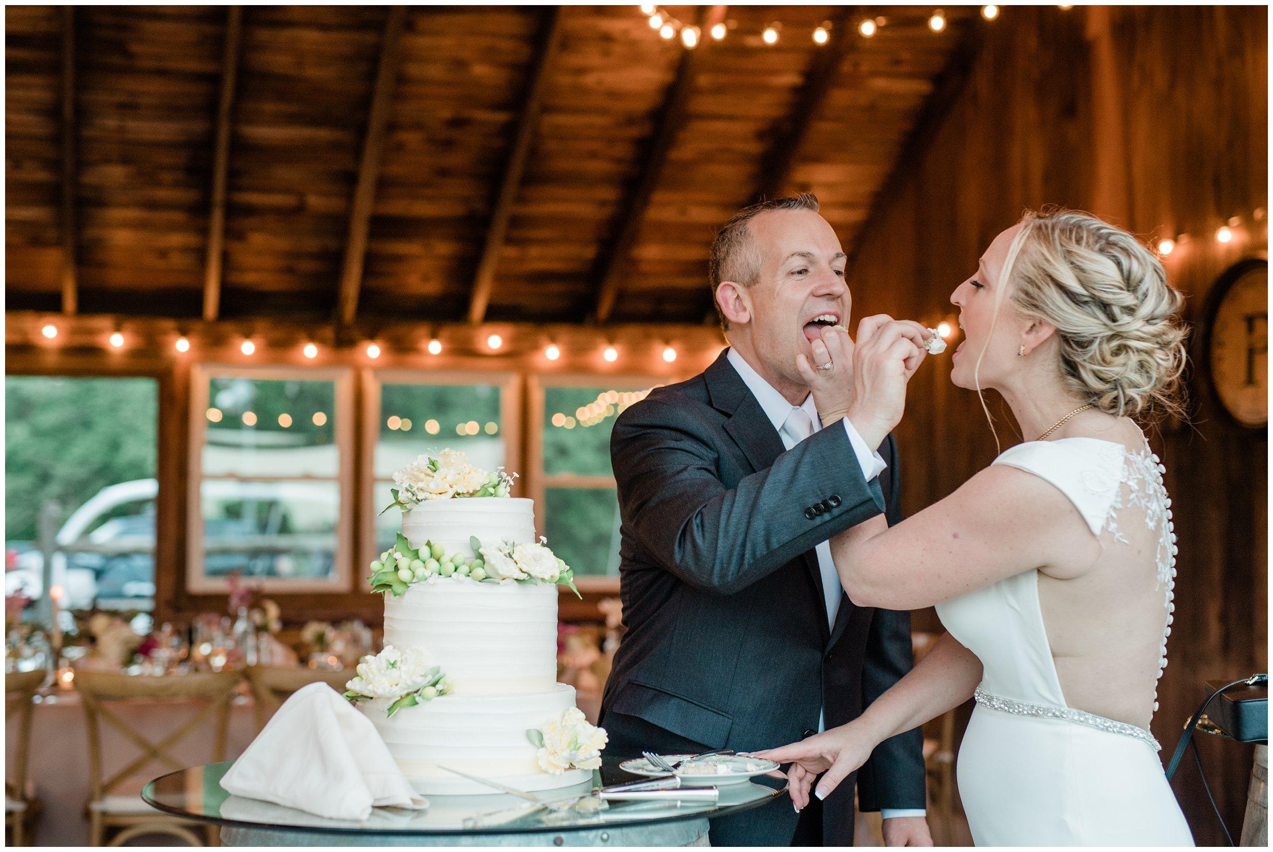 cute newlyweds cutting cake and feeding each other