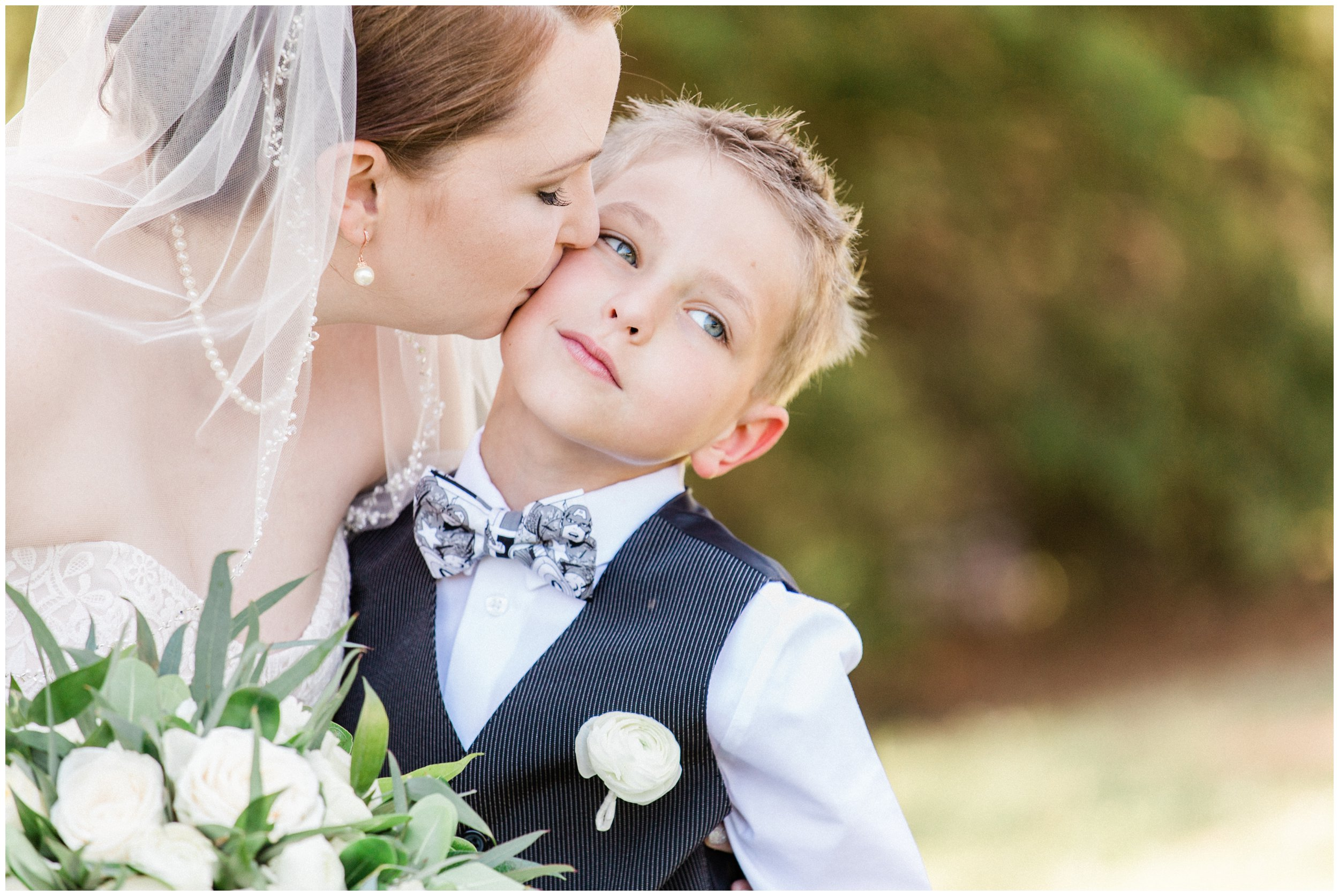 bride kissing son during wedding portraits